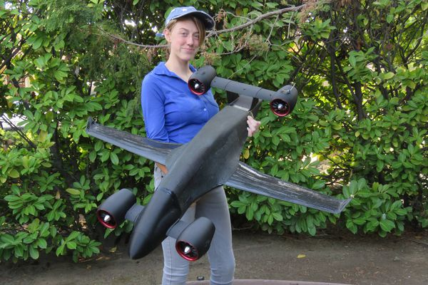 Christine Garrow, daughter of Sabrewing co-founder Oliver Garrow, holds a scale model of the Rhaegal unmanned cargo aircraft that the company intends to test in the airspace around St. Paul Island in the Bering Sea. (Photo courtesy of Sabrewing Aircraft Co.)