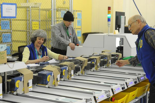 Election workers Lois Hansen, Jack Foster and Jerry Laycock run ballot envelopes through a sorting machine at the Municipality of Anchorage's Ship Creek election headquarters on in Anchorage, AK on Tuesday, April 3, 2018. Foster used pizza boxes to make guards to control the ballots as they land in the precinct stacks. (Bob Hallinen / ADN)