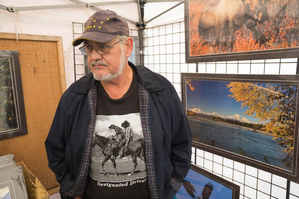Talkeetna photographer Ron Caldwell sells his artwork at an outdoor art bazaar Monday, Aug. 6, 2018 in Talkeetna. (Loren Holmes / ADN)