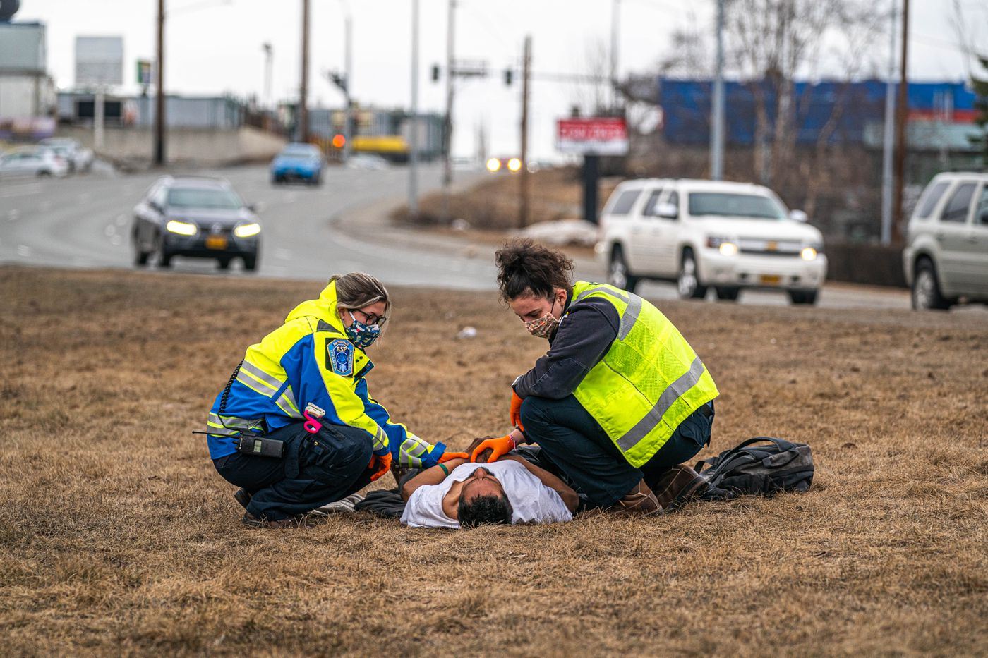 APRIL 17. Anchorage Safety Patrol responders tend to an incapacitated man outside the Sullivan Arena. The arena is serving as a emergency homeless shelter during the coronavirus pandemic. (Loren Holmes / ADN)