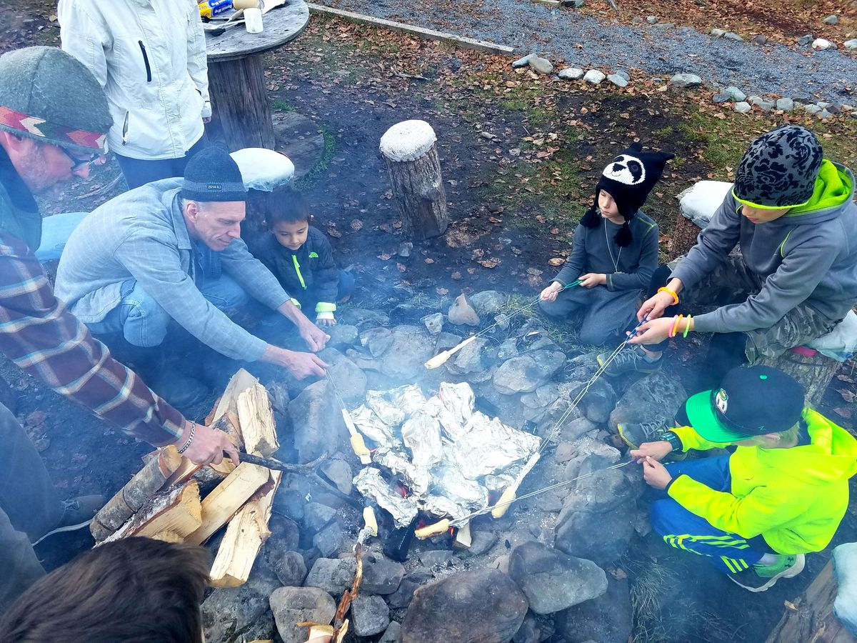 Families cook camper stew and bread during a group campout at Manitoba Cabin. (Erin Kirkland)