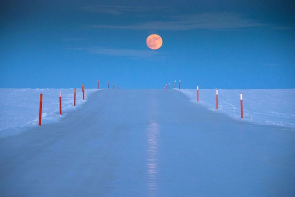 The moon hovers above an ice road at the Point Thomson Project in March 2014. A new Web app, delevoped at UAF, helps state natural resources managers and oil companies make decisions about safe and environmentally sound ice road construction.