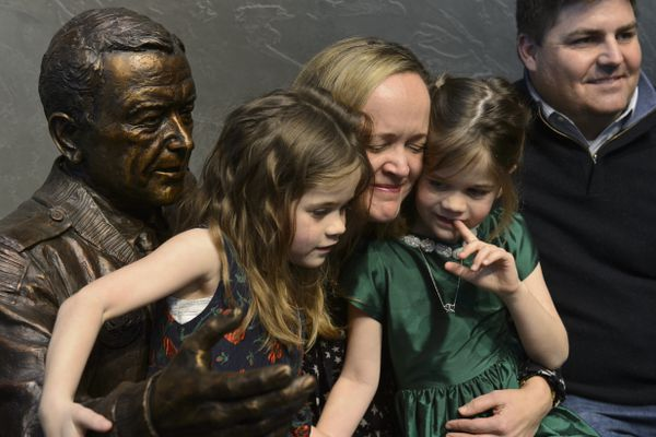 Lily Stevens Becker hugs her 5-year-old twin daughters Megan and Chelsea as they sit with the statue of Stevens Becker's father, Ted Stevens. A bronze statue of Ted Stevens was unveiled during a ceremony at Ted Stevens Anchorage International Airport on February 23, 2019. Stevens, who died in 2010, served in the U.S. Senate for 40 years. (Marc Lester / ADN)