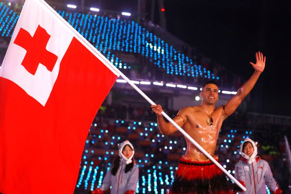 Pita Taufatofua of Tonga carries the national flag during the opening ceremony of the 2018 Winter Olympics on Feb. 9, 2018, in Pyeongchang, South Korea. REUTERS/Kai Pfaffenbach
