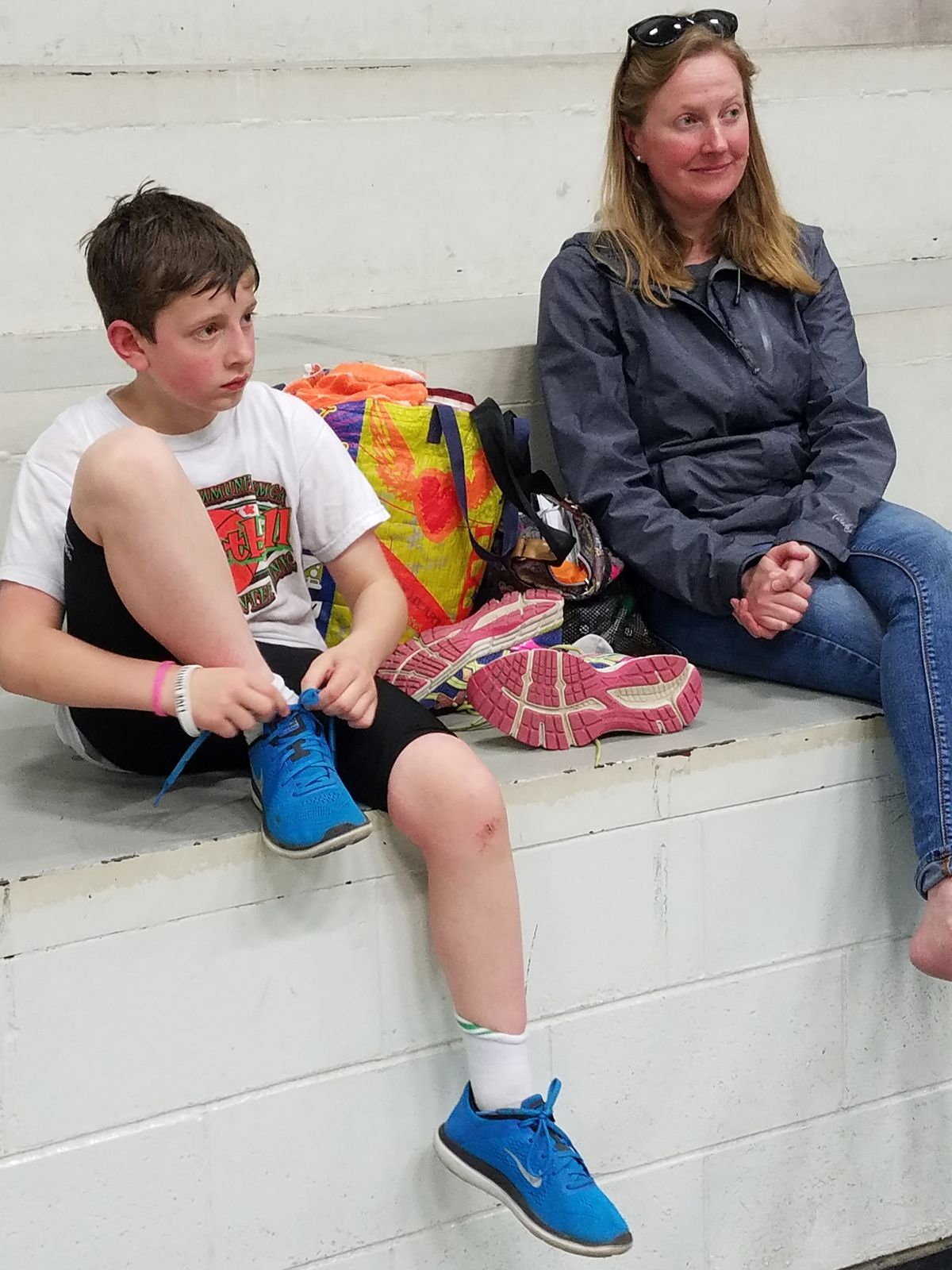 Henry Ash, 9, and his mom Kate Abbott listen to Turnagain Training coach Heather Helzer talk about triathlon strategies after a clinic Saturday at Service High School. Abbott says triathlons have been a fun way for her and Henry to work out together since Abbott is registered for the Gold Nugget Triathlon and Henry is entered in the Trailside and Eagle River triathlons. (Erin Kirkland)