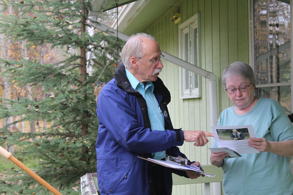 Former Fairbanks borough mayor Luke Hopkins reviews campaign literature with a resident during a door-to-door canvass. Hopkins, a Democrat, is running for a state Senate seat. (Nathaniel Herz / Alaska Dispatch News)
