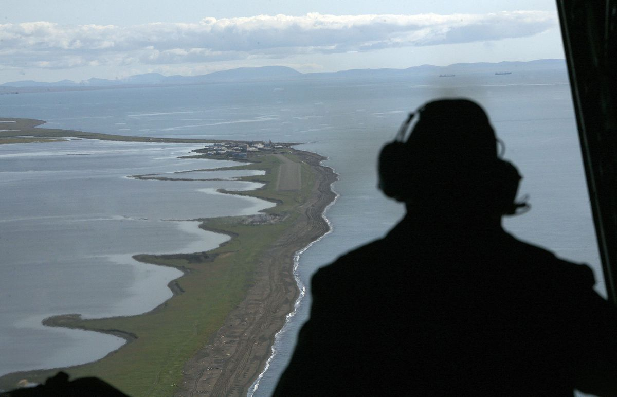 A U.S. Coast Guard aviator surveys the coast near the village of Kivalina during a surveillance flight in the Alaska Arctic, where sea ice has been disappearing much earlier than usual in the spring. (AP Photo/Al Grillo, File)