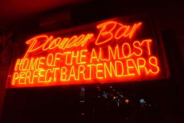 The light of the neon sign at the Pioneer Bar promotes their bartenders along 4th Avenue in Anchorage, Alaska on Wednesday, Sept. 6, 2017. (Bob Hallinen / Alaska Dispatch News)