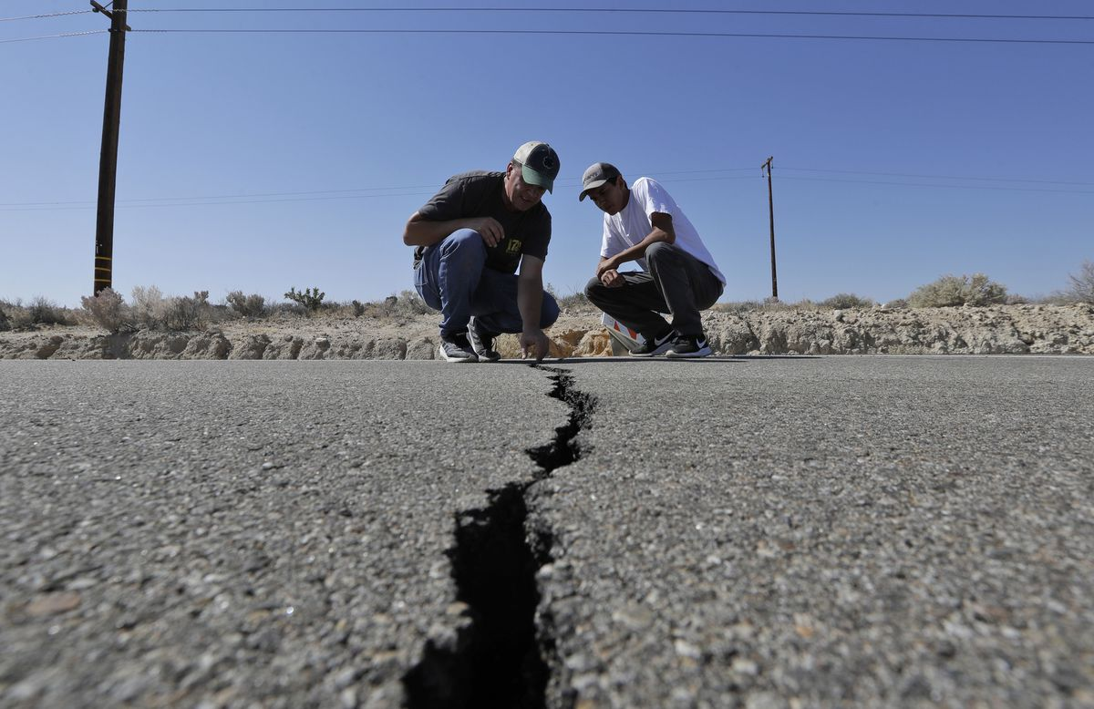 Ron Mikulaco, left, and his nephew, Brad Fernandez, examine a crack caused by an earthquake on highway 178 Saturday, July 6, 2019, outside of Ridgecrest, Calif. Crews in Southern California assessed damage to cracked and burned buildings, broken roads, leaking water and gas lines and other infrastructure Saturday after the largest earthquake the region has seen in nearly 20 years jolted an area from Sacramento to Las Vegas to Mexico. (AP Photo/Marcio Jose Sanchez)