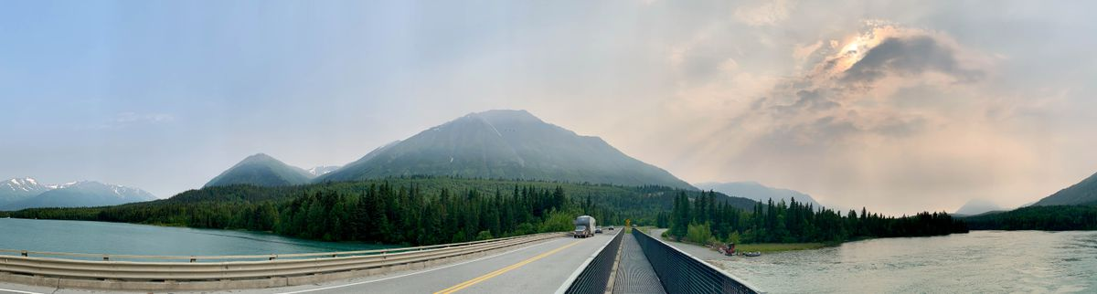 Clouds and smoke from the Swan Lake Fire obscure the sun and mountains above the Kenai River, right, in this panoramic photo taken from the bridge across the river where it leaves Kenai Lake at Cooper Landing on Tuesday, July 9, 2019. (Matt Tunseth / ADN)