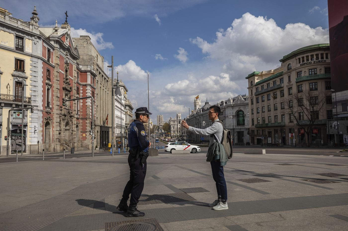A tourist shows the location of his hotel to a local police in downtown Madrid, Spain, Sunday, March 15, 2020. Spain awoke to its first day of a nationwide quarantine on Sunday after the government declared a two-week state of emergency. The government imposed the special measures including the confinement of people to their homes unless shopping for food and medicine, going to and from work, and to meet other basic needs. The vast majority of people recover from the new coronavirus. According to the World Health Organization, most people recover in about two to six weeks, depending on the severity of the illness. (AP Photo/Bernat Armangue)