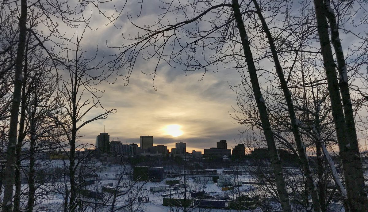 The setting sun silhouettes the Anchorage skyline as viewed from Brown's Point Park on Government Hill on Sunday afternoon, Dec. 23, 2018. (Bill Roth / ADN)