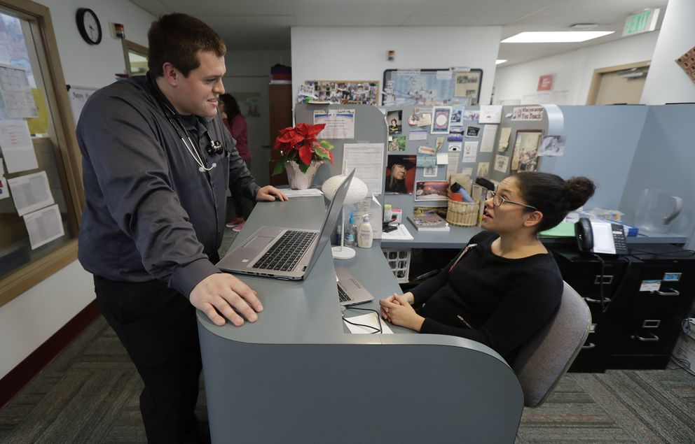 Dr. Alex Kivimaki, left, talks with Dr. Andrea Bachhuber-Beam, as they work at a clinic offering health care and other services operated by the Seattle Indian Health Board, Friday, Jan. 11, 2019, in Seattle. Fallout from the federal government shutdown is hurting hundreds of Native American tribes and entities that serve them. The pain is especially deep in tribal communities with high rates of poverty and unemployment, and where one person often supports an extended family. (AP Photo/Ted S. Warren)