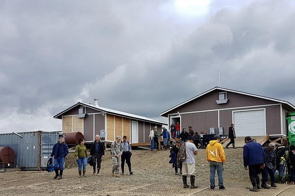 Visitors walk up the main road of Mertarvik to see the new dining hall, community bathrooms and generator. (CHRISTINE TRUDEAU / KYUK)