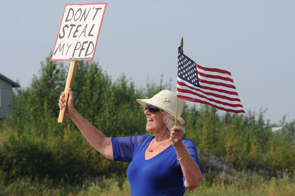 Kathy Hayes waves to motorists on the Parks Highway before the legislative special session at Wasilla Middle School on Monday, July 8, 2019. Hayes said she is