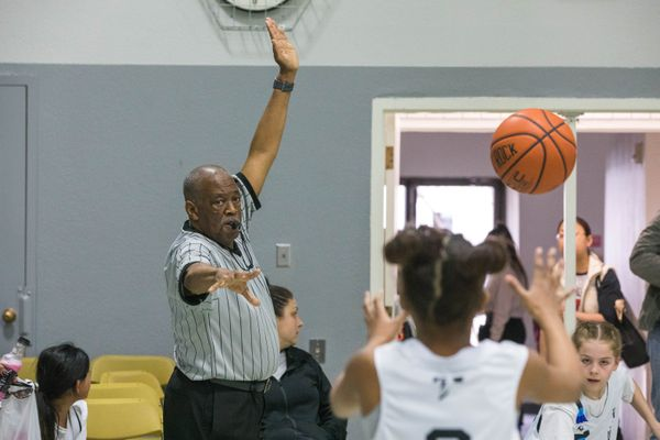 76-year-old Harold Wilson officiates a girls basketball game Saturday, April 6, 2019 at Anchorage Christian Schools. Wilson, who also officiates football and softball, is Anchorage's oldest referee routinely officiating high school football. (Loren Holmes / ADN)