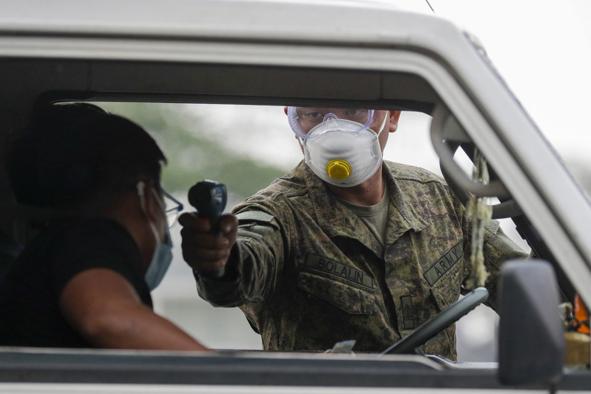 An army trooper uses a thermal scanner to check the temperature of people entering the metropolis at a checkpoint on the outskirts of Quezon city, Philippines. (AP Photo/Aaron Favila)