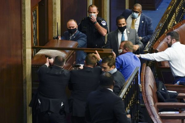 U.S. Capitol Police with guns drawn stand near a barricaded door as protesters try to break into the House Chamber at the U.S. Capitol on Wednesday, Jan. 6, 2021, in Washington. (AP Photo/Andrew Harnik)