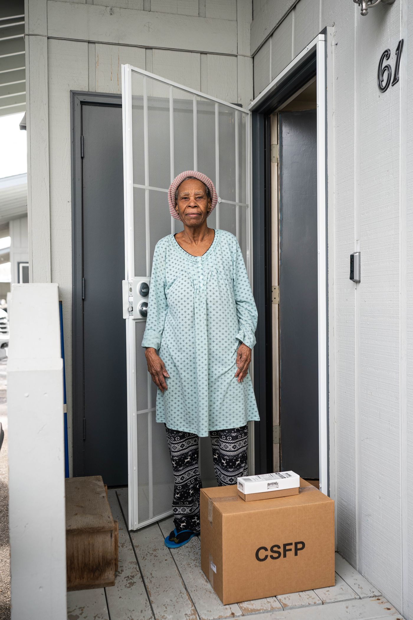MARCH 27. Angela Young, 83, receives a box of food from the Food Bank of Alaska. The non-profit has been partnering with businesses to deliver some food to seniors who are unable to access their normal distribution sites because of restrictions put in place to slow the coronavirus pandemic. (Loren Holmes / ADN)