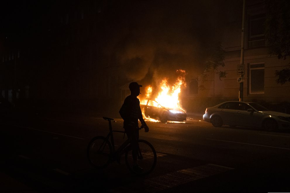 A demonstrator watches a car burn during a protest over the death of George Floyd, Sunday, May 31, 2020, near the White House in Washington. Floyd died after being restrained by Minneapolis police officers. (AP Photo/Evan Vucci)