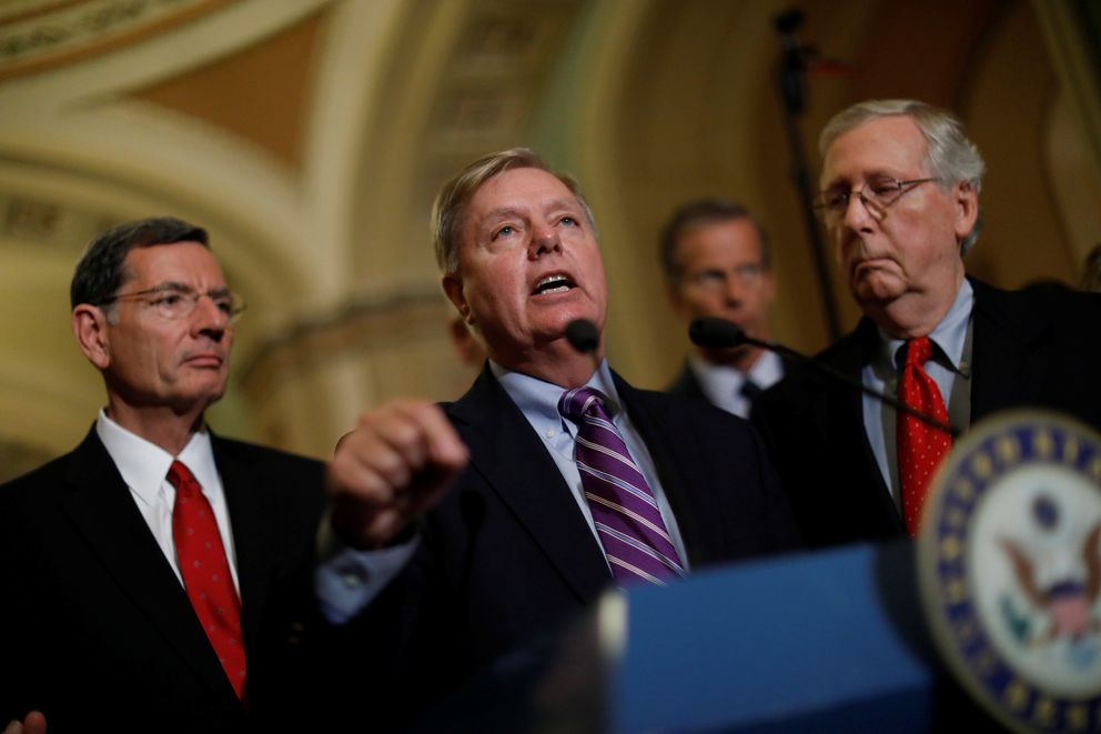 Sen. Lindsey Graham (R-SC), accompanied by Sen. John Barrasso (R-WY), and Senate Majority Leader Mitch McConnell, speaks Tuesday with reporters on Capitol Hill. REUTERS/Aaron P. Bernstein