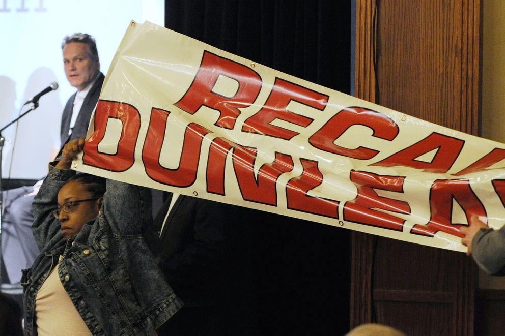 Protesters unfurled a banner as Gov. Mike Dunleavy spoke during a roadshow with Americans for Prosperity in 49th State Brewing Company on Tuesday, March 23, 2019. (Bill Roth / ADN)