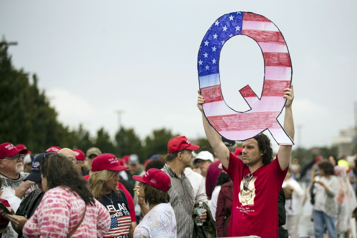 FILE - In this Aug. 2, 2018, file photo, a man holds a sign with a reference to QAnon while waiting to enter a campaign rally with President Donald Trump in Wilkes-Barre, Pa. (AP Photo/Matt Rourke, File)