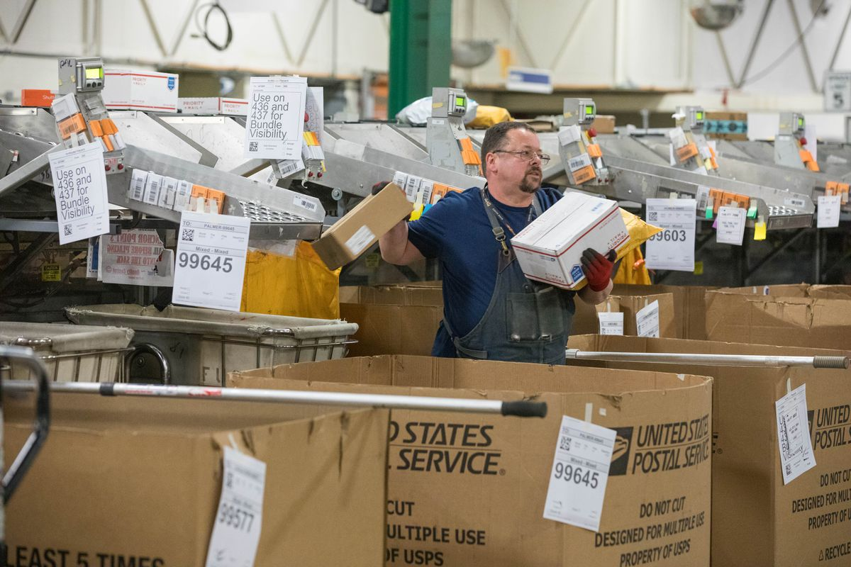 United States Postal Service employee Scott Morphis sorts packages in the Anchorage main office on Dec. 14, 2018. The office is Alaska's largest. (Loren Holmes / ADN archive)