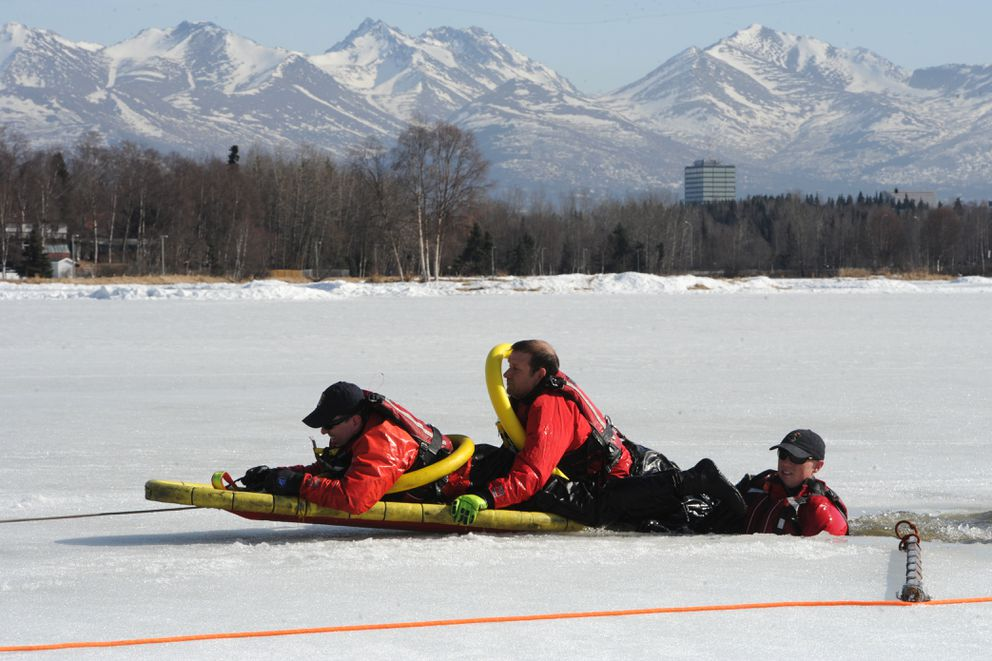 Anchorage Fire Department Capt. Jay Bird, left, is assisted out of the water by Engineer Joel Wagner, center, and Firefighter / Paramedic Jake Lamphier during thin ice training on Westchester Lagoon on Sunday, March 31, 2019. (Bill Roth / ADN)