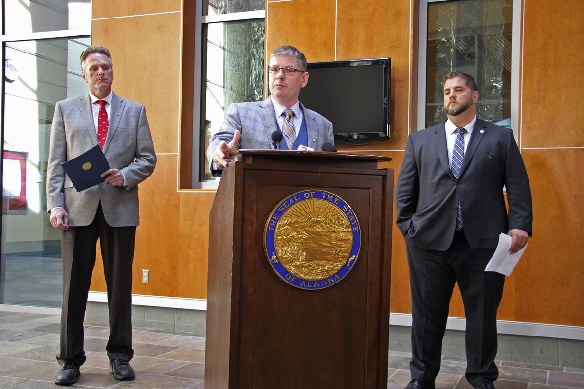 Deputy Alaska health commissioner Albert Wall speaks at a news conference Monday, Aug. 5, 2019, in Anchorage, Alaska, while Gov. Mike Dunleavy, left, and health commissioner Adam Crum, right, look on. State health department officials discussed proposals they are seeking for a study on the feasibility of privatizing Alaska's state-owned psychiatric hospital and announced the Alaska Psychiatric Institute is in good standing with federal requirements. (AP Photo/Mark Thiessen)
