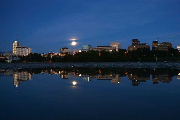 The Anchorage skyline is reflected in a puddle as the moon rises above the city in Anchorage, Alaska on Sunday, August 6, 2017. (Bob Hallinen / Alaska Dispatch News)
