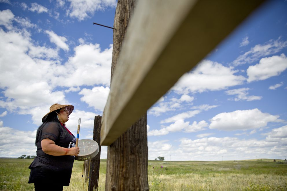Roxanne White, whose aunt was murdered in 1996, sings and drums a women's warrior and honor song created for missing and murdered indigenous women, before joining a search in Valier, Mont., for Ashley HeavyRunner Loring, who disappeared last year from the Blackfeet Indian Reservation, Wednesday, July 11, 2018. For many in Native American communities across the nation, the problem of missing and murdered women is deeply personal. (AP Photo/David Goldman)