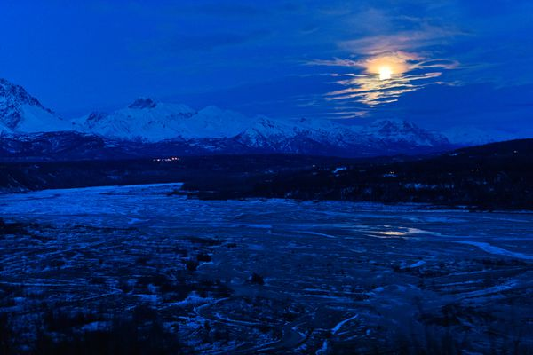 The full moon rises into view from an overlook of the Matanuska River near Palmer on December 11, 2019. (Marc Lester / ADN)