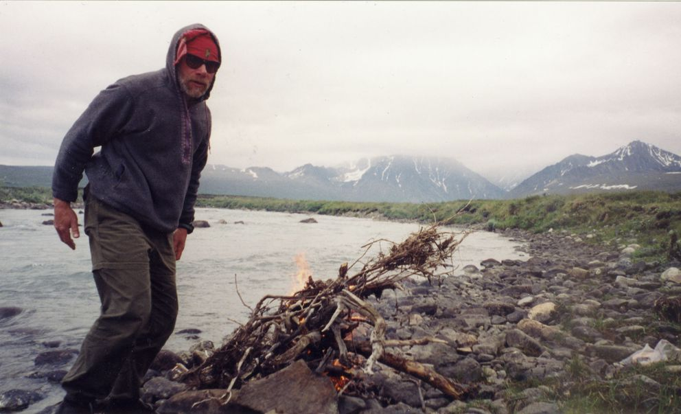 John Branson warms up on the banks of the Mulchatna River just below Turquoise Lake with a partially obscured view of Telaquana Mountain in the background in 2002. (Courtesy of John Branson)