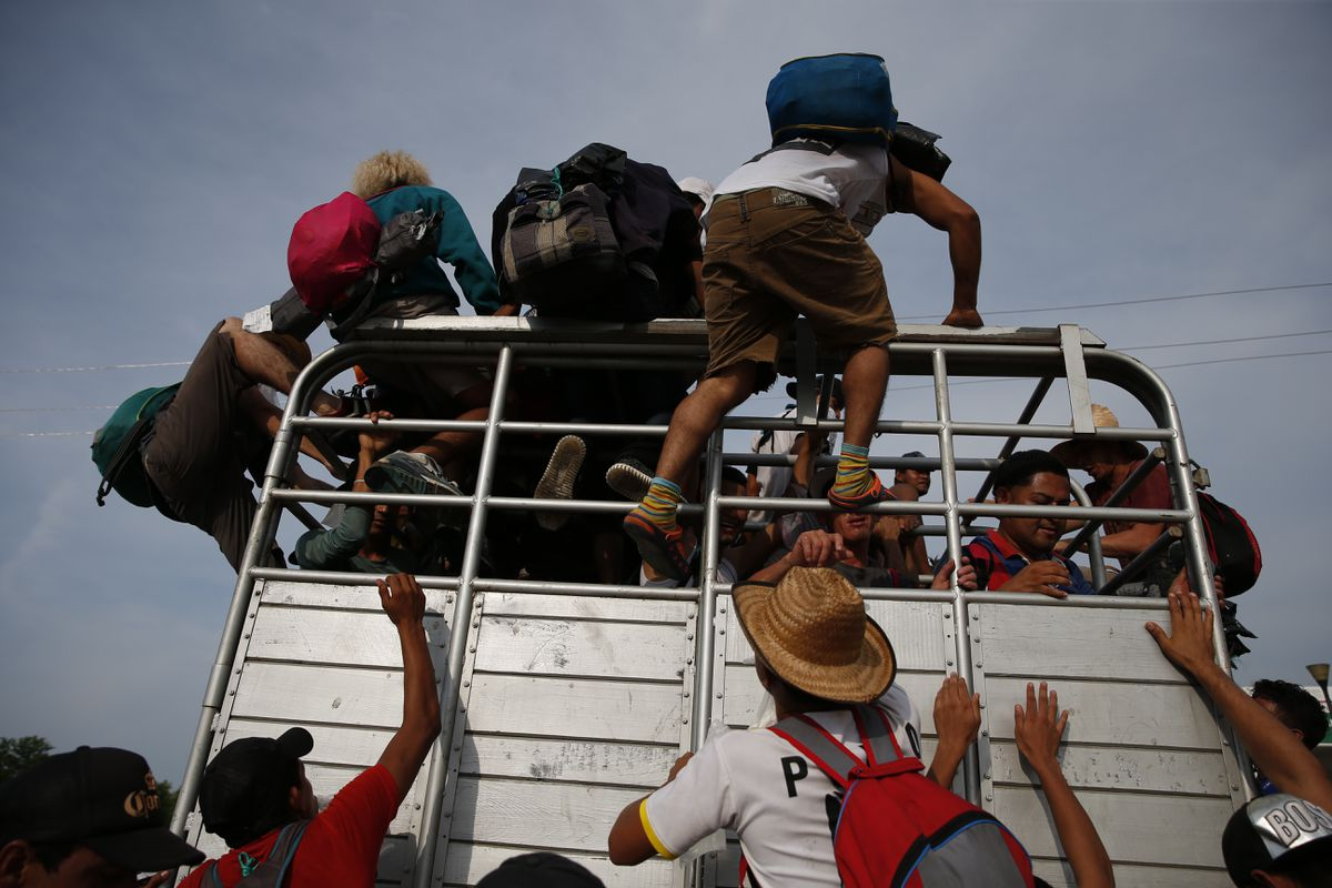 Migrants climb atop a truck as a caravan of thousands of Central Americans continues its slow march toward the U.S. border, outside Arriaga, Mexico, Saturday, Oct. 27, 2018. Many migrants said they felt safer traveling and sleeping with several thousand strangers in unknown towns than hiring a smuggler or trying to make the trip alone.(AP Photo/Rebecca Blackwell)