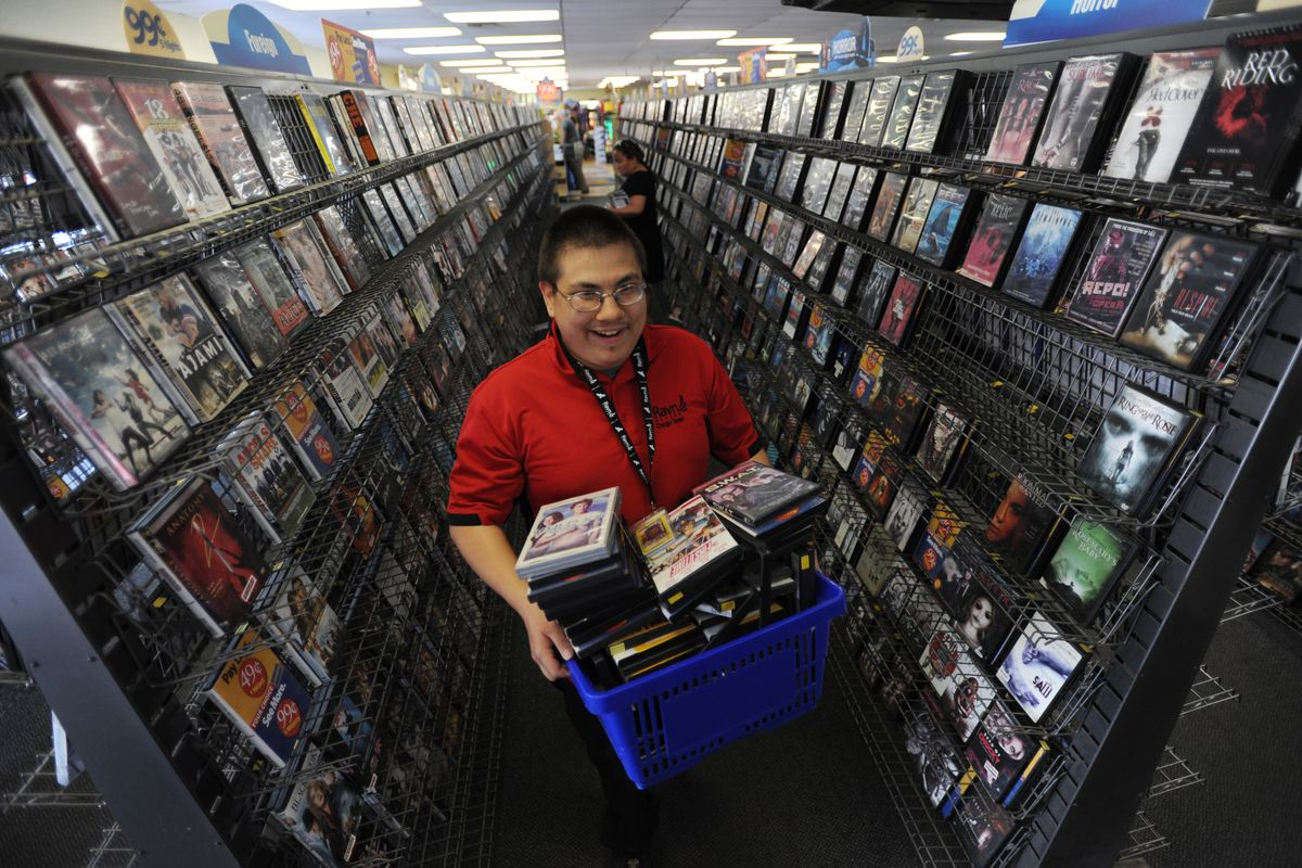 Shawn Fortune heads to the end of the line with a basket full of action and horror movies that he purchased from the Blockbuster store on DeBarr Road on Tuesday, July 17, 2018.  (Bill Roth / ADN)