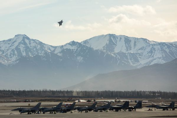 An Air Force F-22 takes off from its home base at Joint Base Elmendorf-Richardson Tuesday, May 2, 2017 during the Northern Edge training exercise. On the tarmac are F-16s and F-15s. (Loren Holmes / Alaska Dispatch News)