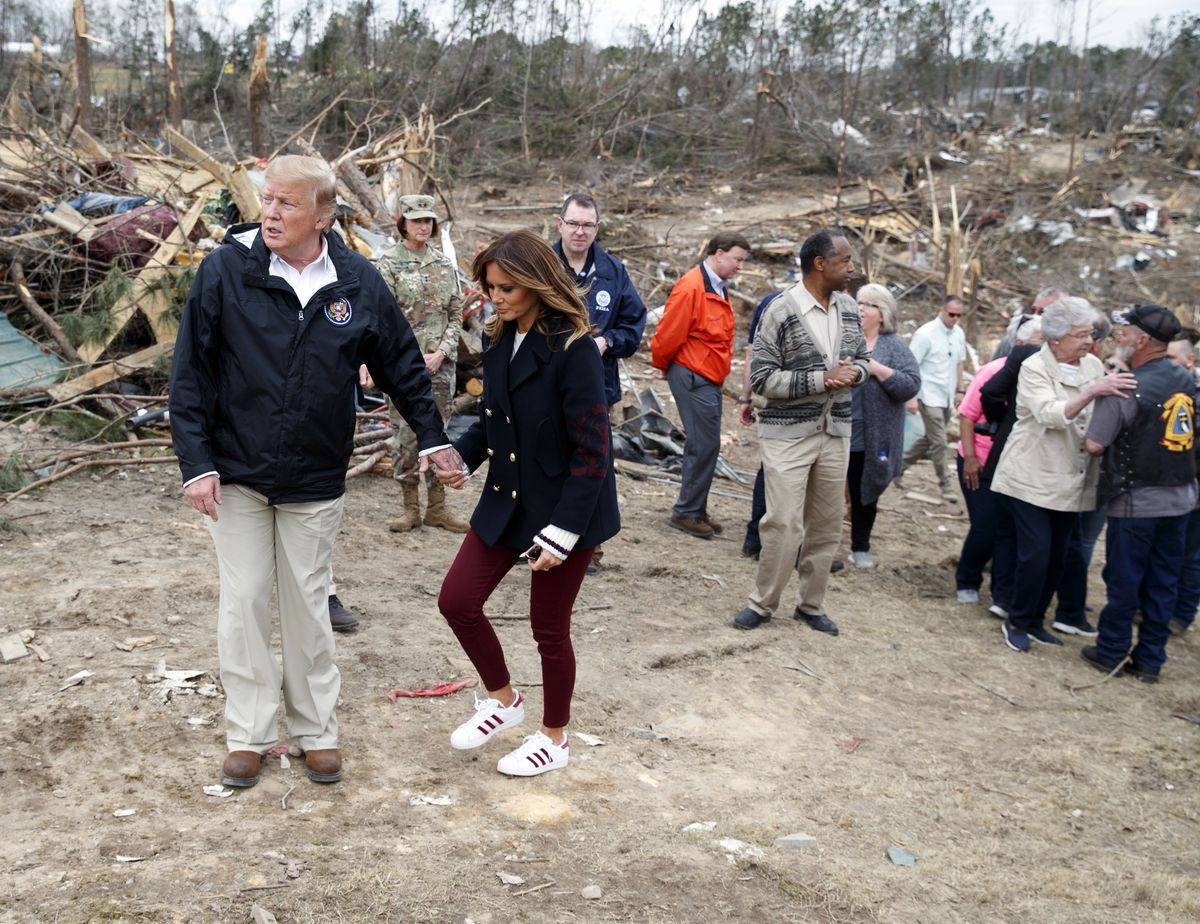 President Donald Trump and first lady Melania Trump talk with people Beauregard, Ala., Friday, March 8, 2019, as they travel to tour areas where tornados killed 23 people in Lee County, Ala. (AP Photo/Carolyn Kaster)