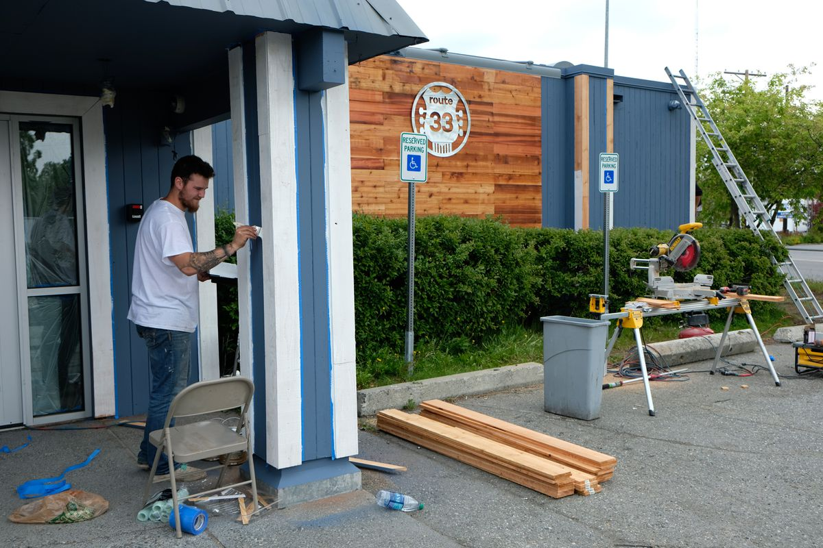 Patrick Nowka paints the exterior of Route 33 on Tuesday. The Spenard Road bar used to be known as the TapRoot.  (Marc Lester / Alaska Dispatch News)