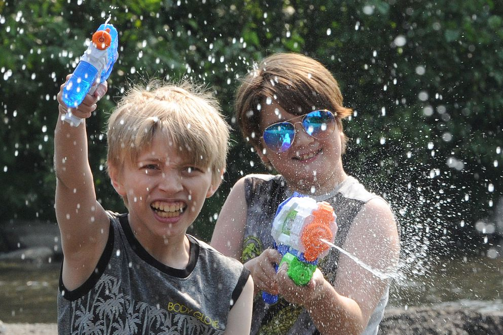 Wyatt Thompson, 11, and Lyric Thompson, 10, played with water guns while wading in Campbell Creek on a warm Monday, July 8, 2019. (Bill Roth / ADN)