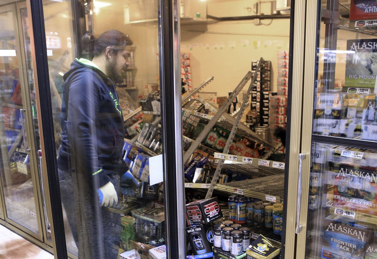 Aisoli Lealasola prepares to clean up fallen cases of beer in a cooler at a liquor store, Value Liquor, after an earthquake on Friday, Nov. 30, 2018, in Anchorage, Alaska. Owner Mary Funner says beer, wine and other bottled alcohol was strewn throughout store aisles after the quake. She considered closing Friday until customers began lining up. They were allowed to come in in small groups.