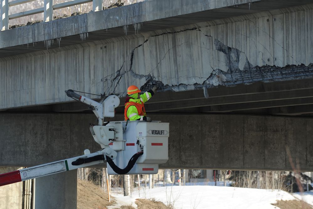 A Department of Transportation worker chips loose concrete from the South Eagle River Overpass after a modular ATCO style unit being transported on a trailer struck the overpass in Eagle River, Alaska on Wednesday, March 17, 2018. The impact sheared off the roof of the module. (Bob Hallinen / ADN)