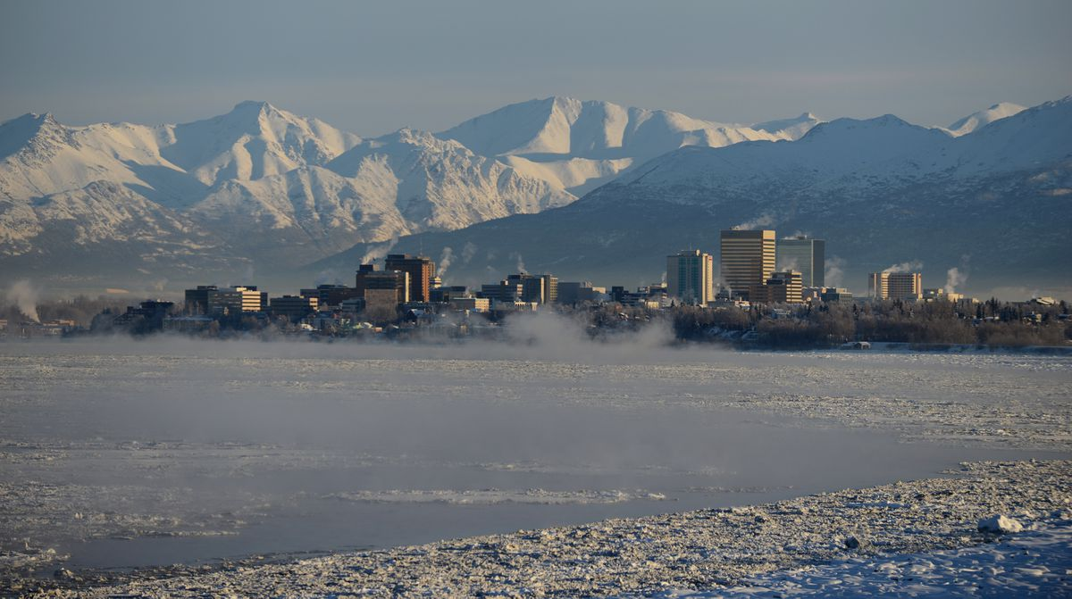Steam rises from buildings and fog rises off Cook Inlet on a cold morning in downtown Anchorage, Alaska on Wednesday, January 18, 2017. The snow-covered Chugach Mountains rise in the background. (Bob Hallinen / ADN)