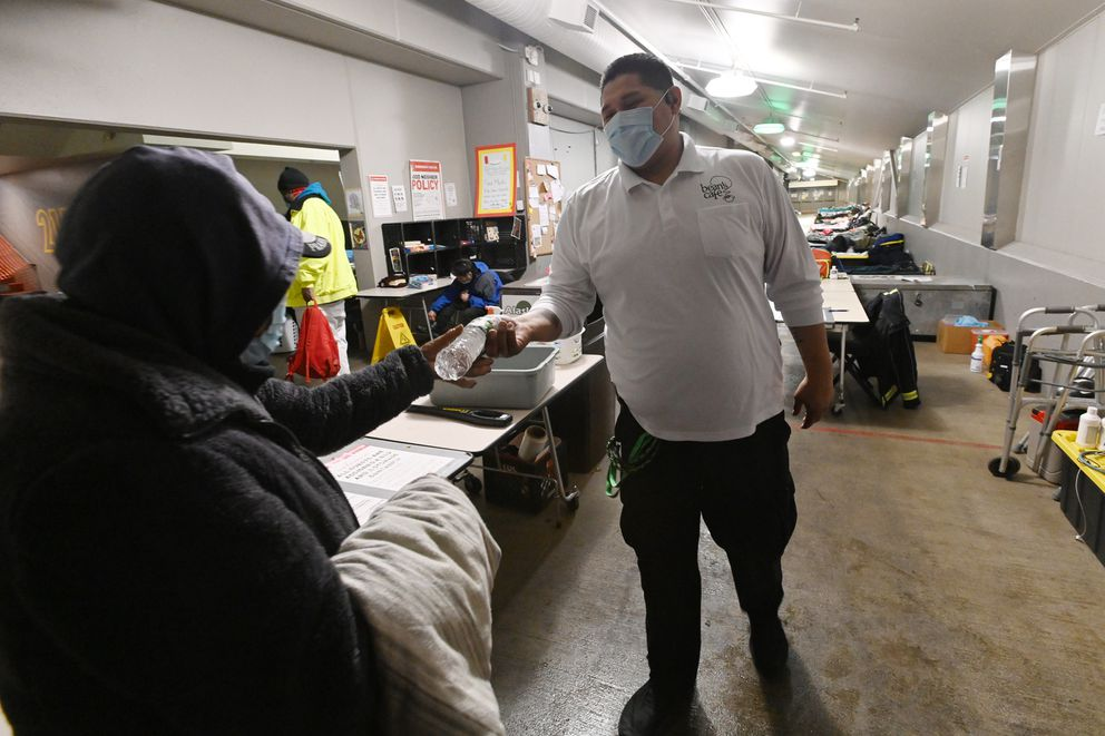 Bean's Cafe security guard Roberto Santiago hands a water bottle to Ella Luther after filling it for her when she was denied access to the Sullivan Arena homeless shelter after it reached full capacity on rainy Wednesday evening, Oct. 14, 2020. (Bill Roth / ADN)