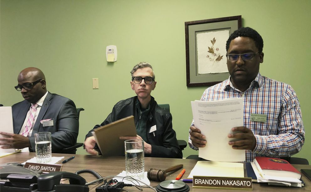 Alaska Human Rights Commission members Marcus Sanders, left, David Barton, middle, and chairman Brandon Nakasato are shown at the conclusion of a commission meeting Monday, April 1, 2019, in Anchorage, Alaska. The commission went into executive session for nearly three hours but recessed when it could not come to a conclusion on the fate of Marti Buscaglia, its executive director after Alaska Gov. Mike Dunleavy requested an investigation following her social media complaint about a pickup parked in the commission's lot that had a 'Black Rifles Matter ' sticker. (AP Photo/Mark Thiessen)