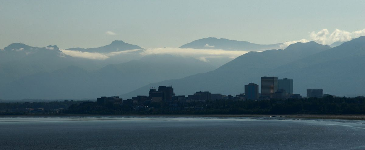 The Chugach Mountains are hazy as they backdrop the Anchorage skyline as seen from west Anchorage, Alaska on Thursday, July 6, 2017. (Bob Hallinen / Alaska Dispatch News)