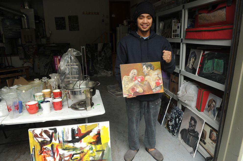 Niklaus Noceda and his interpretation of the 2009 Manny Pacquiao vs. Miguel Cotto fight at the Kempton Hills garage sale on Saturday. The UAA student sold his artwork in the garage where he creates his paintings. (Bob Hallinen / Alaska Dispatch News)