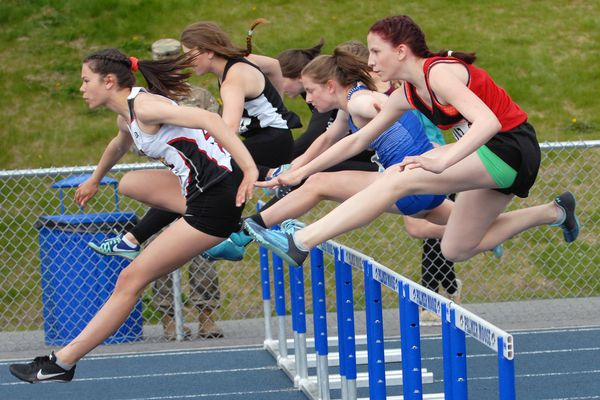 Competitors in the Division II girls 100 hurdles clear the first hurdle during a preliminary heat at the ASAA/First National Bank Alaska Track and Field Championships on Friday, May 24, 2019 at Machetanz Field in Palmer. (Matt Tunseth / Chugiak-Eagle River Star)