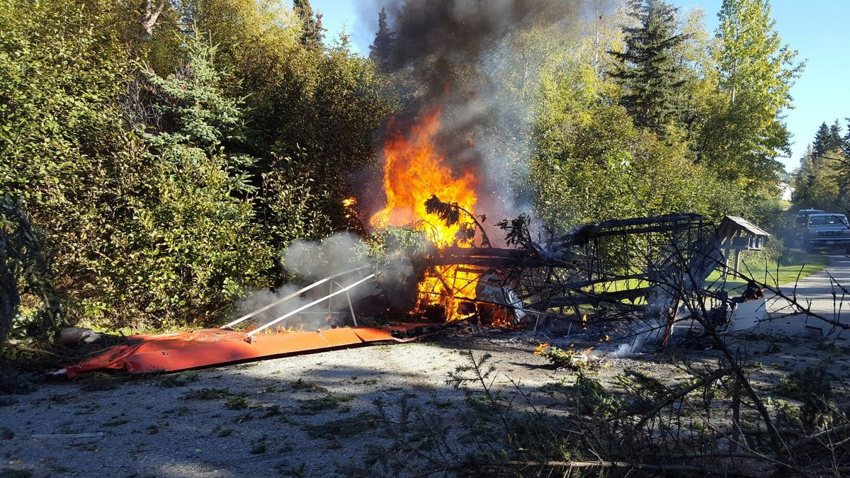 A plane caught on fire after crashing in the Hillside neighborhood of Anchorage. (Photo by Jason Thompson)