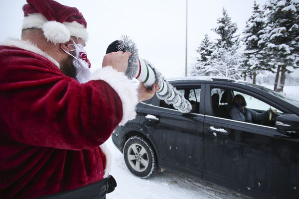 Derrick Kubosh, who works Tech Support for the Anchorage School District, passes candy canes through a chute to children and parents as they sit in their cars outside Lake Otis Elementary School in Anchorage on Wednesday, Dec. 16, 2020. (Emily Mesner / ADN)